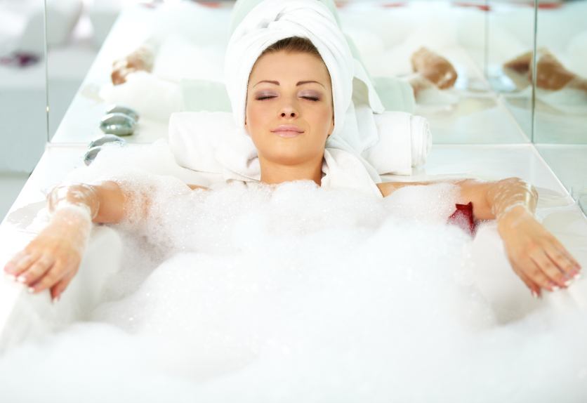 Young woman lying in bath tub with her eyes closed